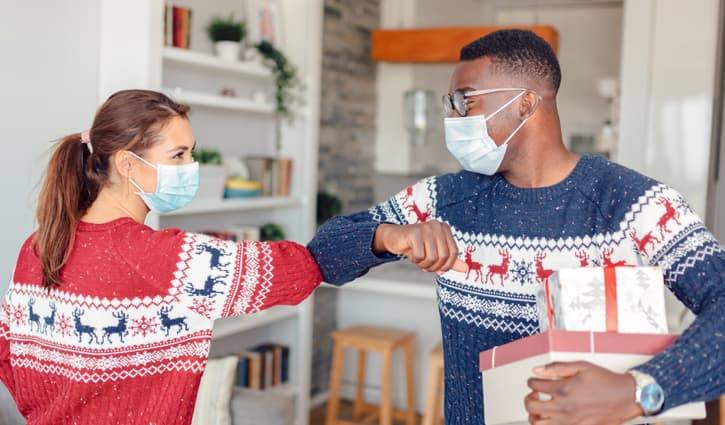 A woman and man wearing masks and holiday sweaters elbow bump while exchanging gifts.