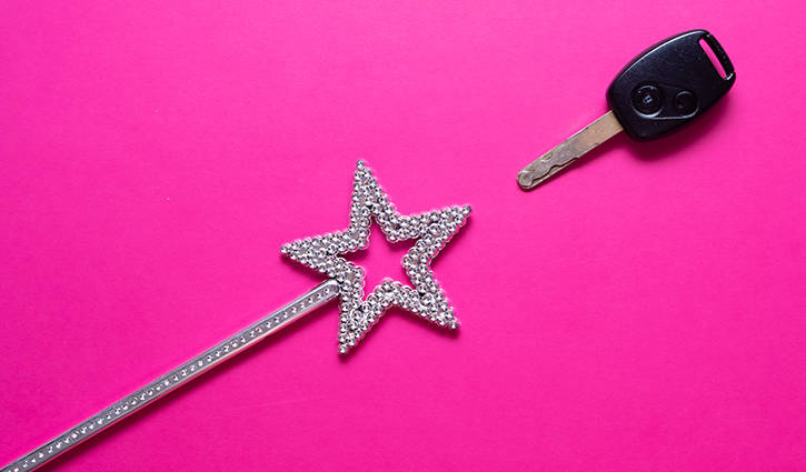 Car key and magic wand on pink background
