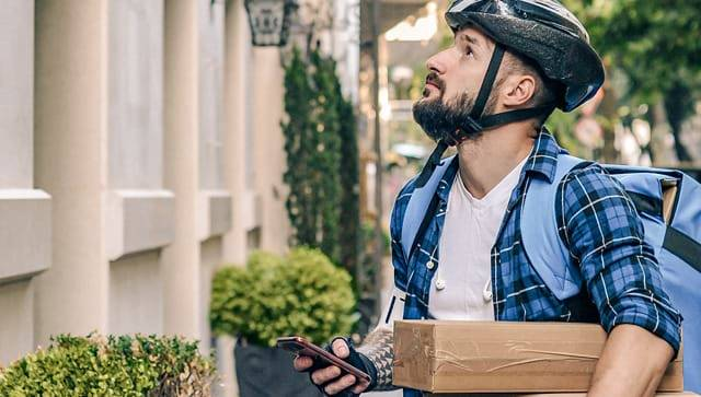 Delivery man with cell phone and packages.