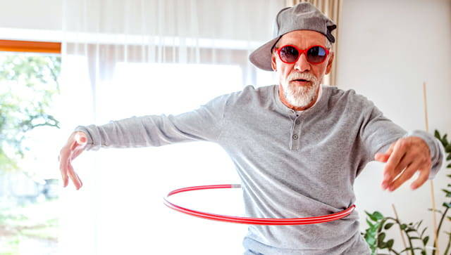 Older gentleman dressed like a young person with backward cap, red sunglasses and playing with a hula hoop.