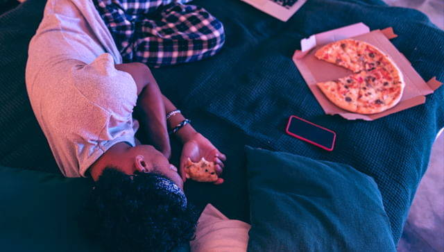 Sleeping boy next to pizza and phone.