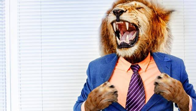 Man in suit with head and paws of a lion.