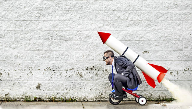 man in suit on tricycle with rocket on his back