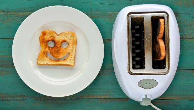 Toast with smiling face carved into it, laying on plate next to toaster.