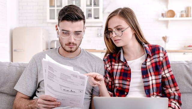 Millennial man and woman sit together and look at bills.