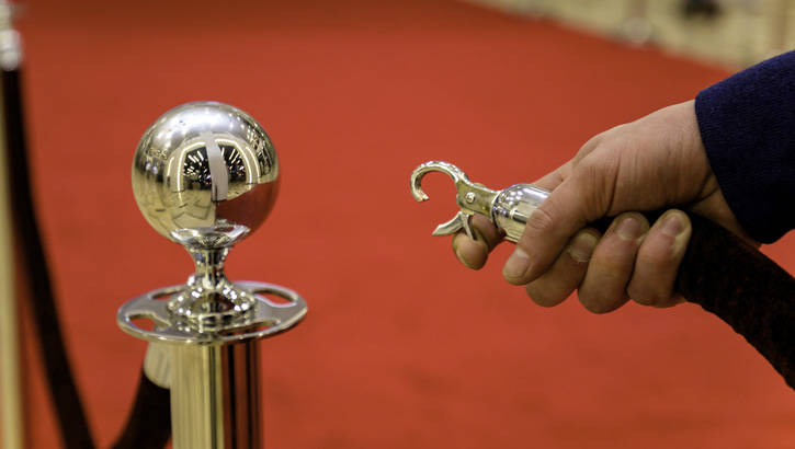 Person opening a red carpet stanchion