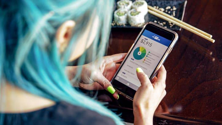 Millennial woman with blue hair checking her budget on her cell phone.