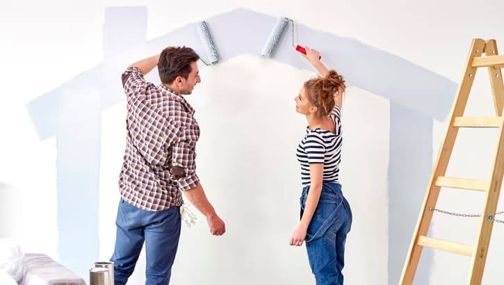 Happy couple painting a wall in their apartment.