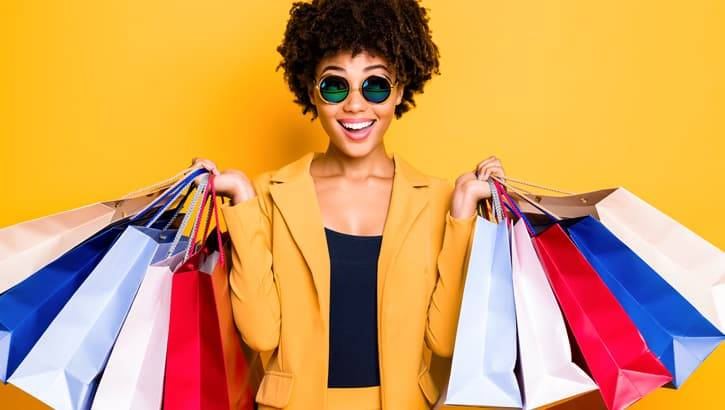Millennial woman in yellow outfit holding colorful shopping bags.