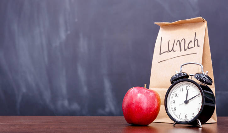 brown paper lunch sack on desk with apple and clock