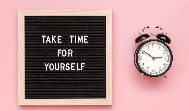 sign with text that says take time for yourself next to a vintage alarm clock on a pink background