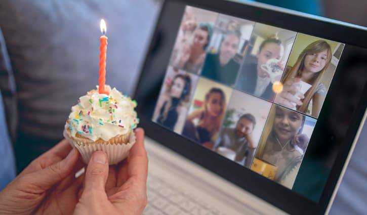 Group video chat celebrating birthday, with cupcake and candle.