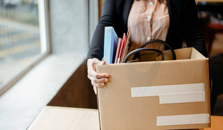 Woman in business attire carrying box of personal office supplies out of office.