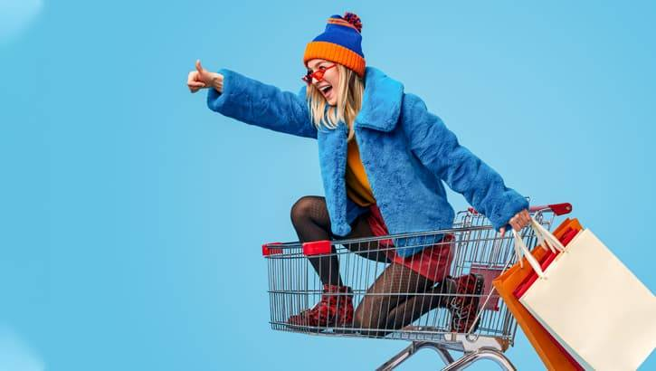 Blond millennial woman wearing blue and orange riding in a shopping cart with shopping bags.