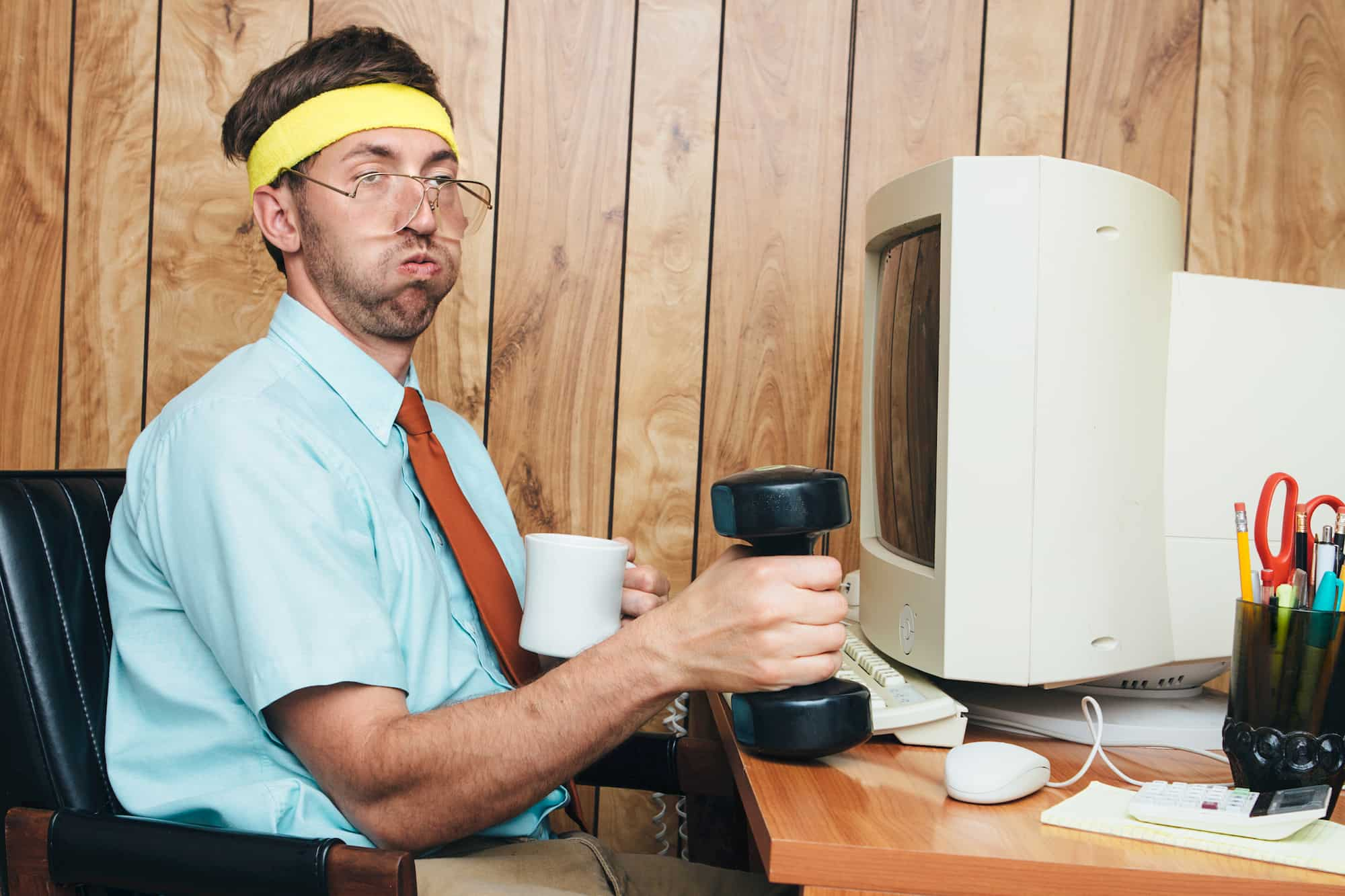 Man at a computer desk with a coffee mug in one hand and a weight in the other, wearing a shirt and tie with exerted expression.